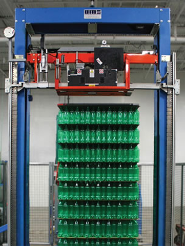 Rows of green plastic bottles being stacked on the bundling machine.