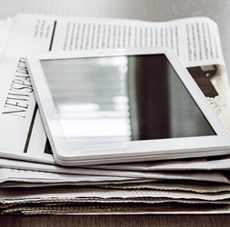 Stack of news with a tablet on top.